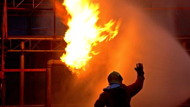 4k feuerwehrleute löschen brand in ölraffinerie - unfall und katastrophe stock-videos und b-roll-filmmaterial