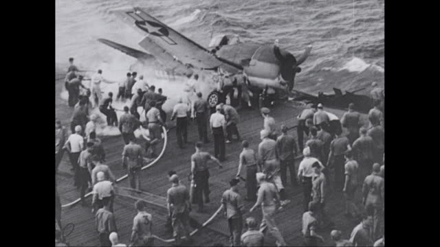 WS Firefighters extinguishing fire on aircraft carrier, crashed burning plane on deck of carrier / United States