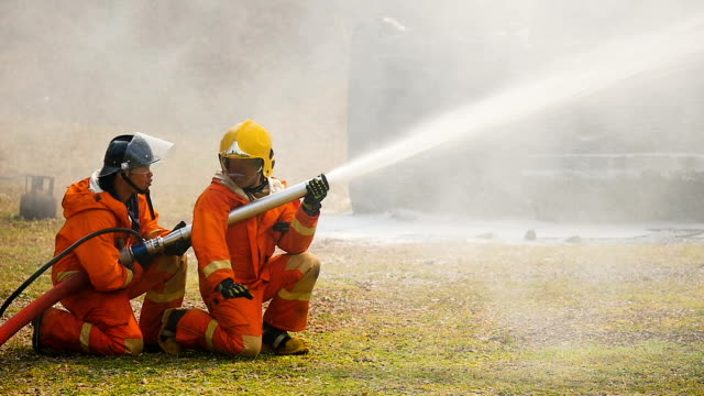 Firefighters fighting a fire operation, Foam spray by high pressure nozzle to truck fire after the accident