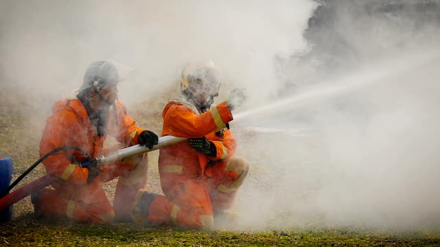 vídeos de stock e filmes b-roll de firefighters fighting a fire operation, foam spray by high pressure nozzle to truck fire after the accident - bombeiro