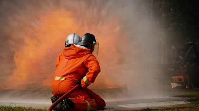 feuerwehrleute kämpfen ein feuer betrieb, spritzwasser durch hochdruckdüse surround mit rauch, feuer, löschen feuerwehr ein auto - retter rettungsaktion stock-videos und b-roll-filmmaterial