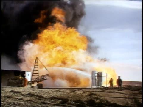 1975 ws firefighters fighting oil fire / united states - släcka bildbanksvideor och videomaterial från bakom kulisserna
