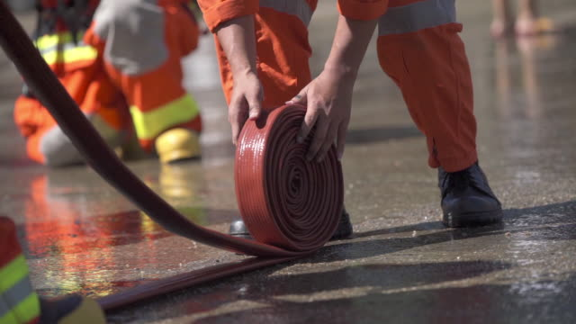 stockvideo's en b-roll-footage met brandweerlieden voltooien een baan - fire hose
