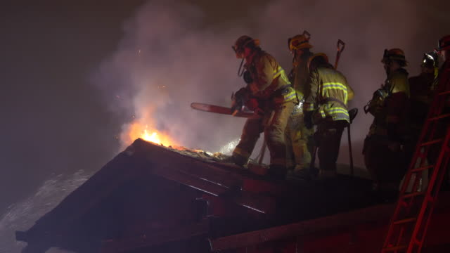 firefighters firemen on a house roof fighting to put out a fire at night. - rescue worker stock videos & royalty-free footage