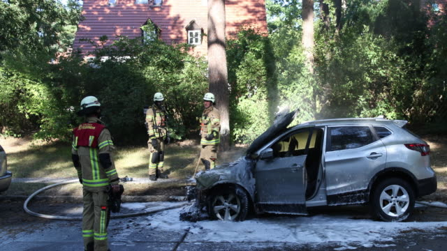 firefighters from the berlin fire brigade zehlendorf district extinguishes a burning car parked in a forest settlement with over 300 houses and pine... - protection stock videos & royalty-free footage