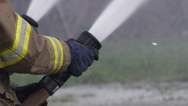 stockvideo's en b-roll-footage met firefighter's hands hold a streaming hose and raise the nozzle - fire hose