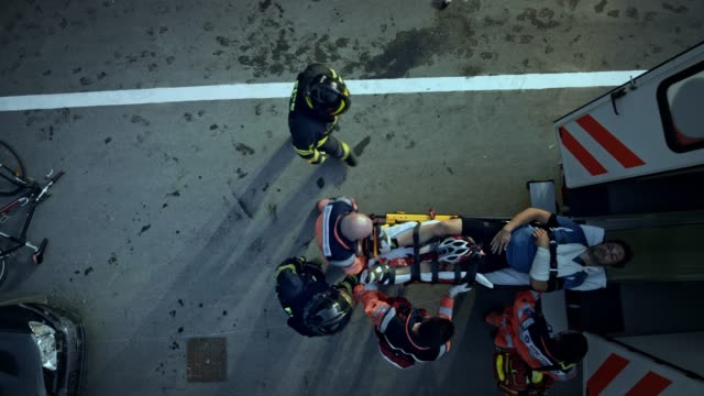 CS Firefighters helping the paramedics load the injured cyclist into the ambulance