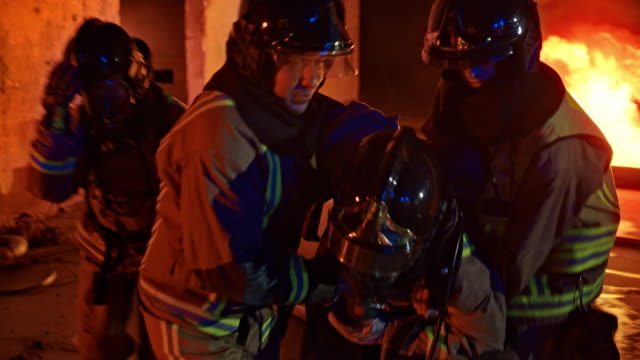 firefighters helping their injured fellow firefighter - firefighter stock videos and b-roll footage