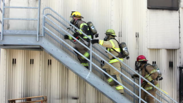 firefighters in gear climbing stair to warehouse door - rescue worker stock videos and b-roll footage