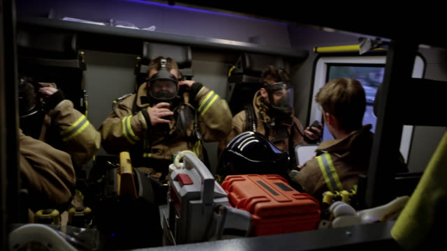 firefighters in the back of the fire truck preparing themselves on the way to the fire scene - fire protection suit stock videos & royalty-free footage