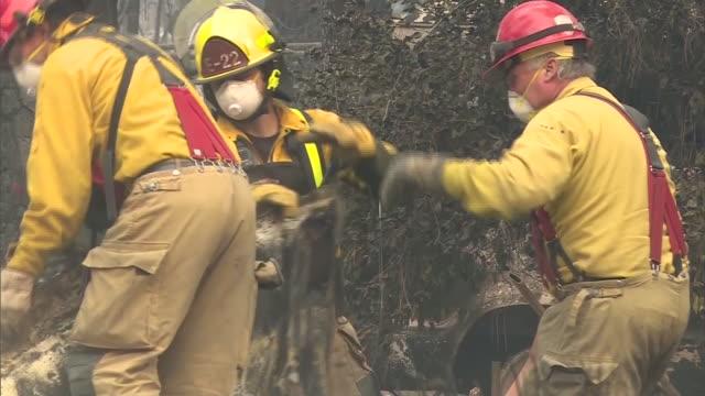 ktla firefighters looking through rubble after woolsey fire destroys home - malibu stock-videos und b-roll-filmmaterial