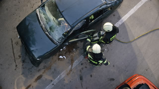 vídeos de stock e filmes b-roll de cs firefighters opening the crashed car door with hydraulic spreaders - impacto