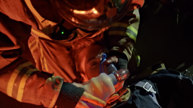 firefighters placing a bag valve mask over the face of their fellow firefighter - rescue worker stock videos & royalty-free footage