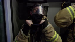 Firefighters placing the masks over their faces and communicating in the back of the fire truck heading to the scene of the fire