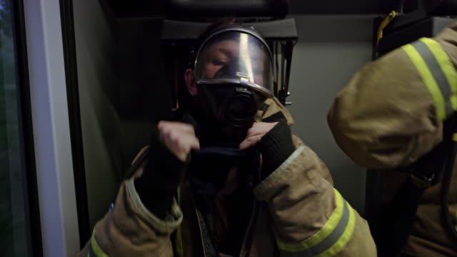 firefighters placing the masks over their faces and communicating in the back of the fire truck heading to the scene of the fire - fire protection suit stock videos & royalty-free footage