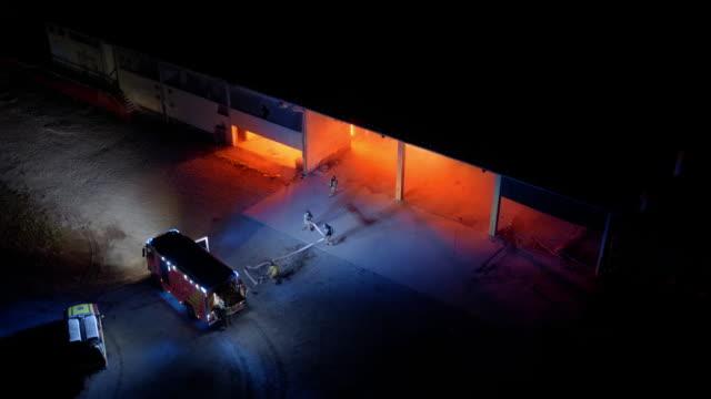 stockvideo's en b-roll-footage met luchtfoto brandweerlieden voorbereiding van de brandslang op de scène van de brand bij nacht - fire hose