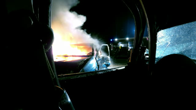 pov firefighters putting out car fire at night and water splashes into the camera - road accident stock videos & royalty-free footage