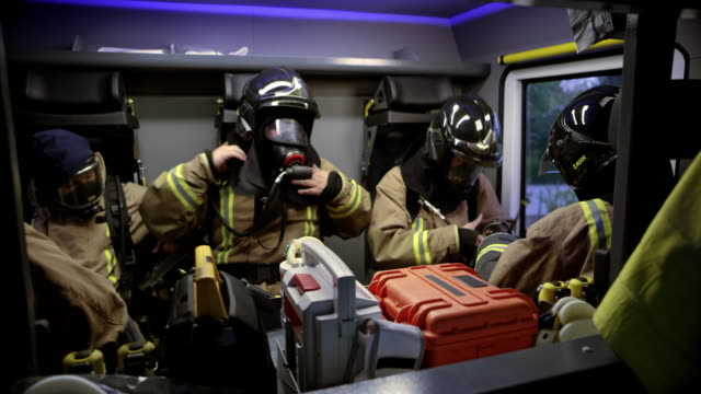 firefighters putting their masks on in the fire truck on their way to the fire scene - fire engine stock videos & royalty-free footage