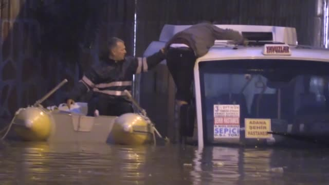 Firefighters rescue a man from a midibus stuck on a flooded road following a heavy rain in Adana Turkey on January 23 2018