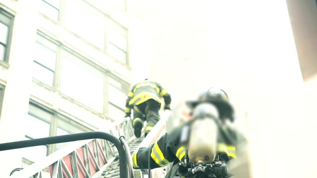 Firefighters rescuing victim from an apartment building fire in New York City