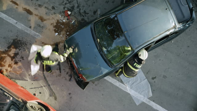 vídeos de stock e filmes b-roll de cs firefighters running to the people in a crashed car and saving them by cutting the roof off - impacto