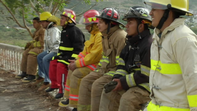 ms firefighters sitting side by side on wall, ecuador - side by side stock videos & royalty-free footage