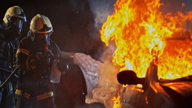vídeos de stock e filmes b-roll de slo mo firefighters spraying foam onto a burning vehicle at night - impacto