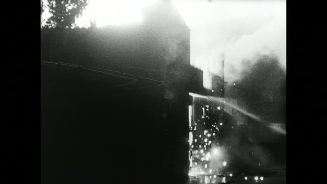 MONTAGE Firefighters spraying water onto burning building during night-time air raid / London, England, United Kingdom