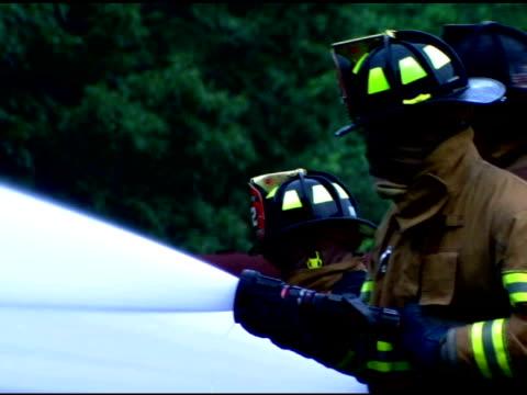 firefighters spraying water - 消火ホース点の映像素材/bロール