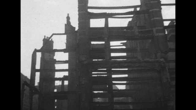 vídeos y material grabado en eventos de stock de firefighters standing on pile of rubble in street across giant ladder to destroyed skeleton of building / portion of ext bldg collapsing into st /... - el blitz
