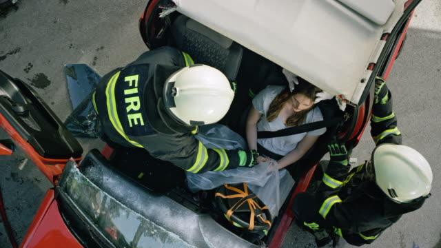 Pompiers de CS parler au conducteur blessé dans l'accident de voiture après avoir pris le toit de la voiture s'est écrasé