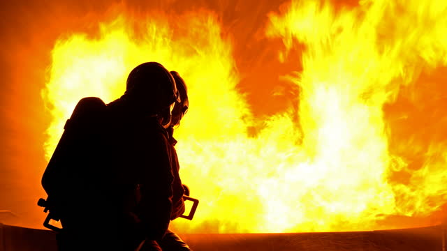 消防ホースを使用した4k消防士が火を消す - 消火ホース点の映像素材/bロール