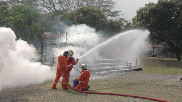 フィールドスローモーションで消火フォームを使用する消防士 - 消防士点の映像素材/bロール