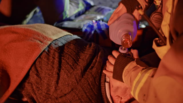 firefighters ventilating a man with a bag valve mask at the fire scene at night - valve stock videos & royalty-free footage