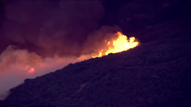 KTLA Firefighters were battling a wildfire in the hills along the 91 Freeway on the far eastern edge of Anaheim on Monday and there's concern that...