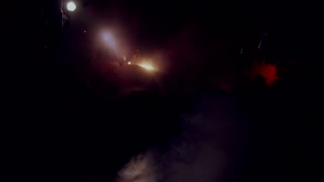 Firefighters with a flashlight extinguish a building at night with a hose