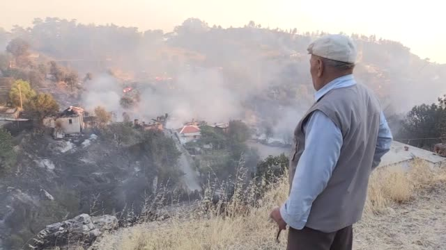 firefighters work to extinguish a forest fire that spread into a village in the mentese district of mugla turkey on september 06 2017 villagers react... - mugla province stock videos & royalty-free footage