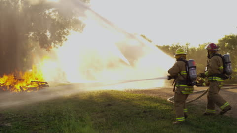 firefighters work to extinguish a roaring bonfire, burning pile of brush and debris - five people stock videos & royalty-free footage