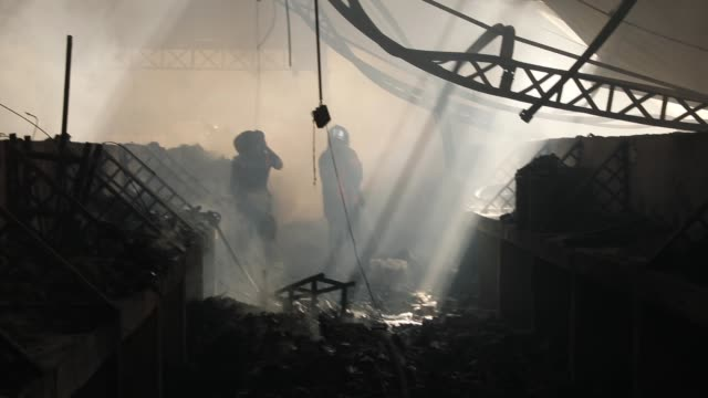 firefighters work to put out a blaze at portauprince's historic iron market on february 13 2018 in portauprince haiti hundreds of locals vendors lost... - insel hispaniola stock-videos und b-roll-filmmaterial