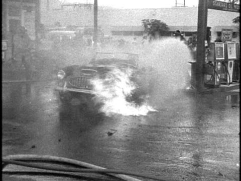 firefighters working to extinguish an mg convertible car on fire, burning near the gasoline pumps of a standard oil gas station/ honolulu, oahu,... - 有事点の映像素材/bロール