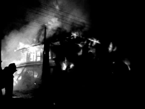 firefighters working to extinguish blazing house fire at night/ ws pan firefighters seen through wire fence spraying water on burning house/ honolulu... - 1975年点の映像素材/bロール
