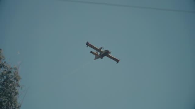 brandbekämpning flygplan och helikoptrar släcka en vild brand i toscana, italien - släcka bildbanksvideor och videomaterial från bakom kulisserna