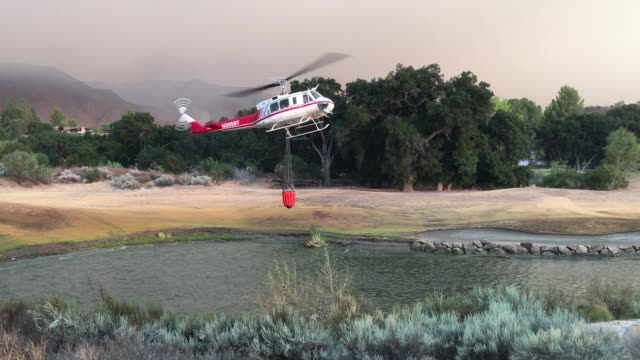 firefighting helicopters refill water as firefighters continue to battle the sand fire near santa clarita ca july 23 2016 - santa clarita 個影片檔及 b 捲影像
