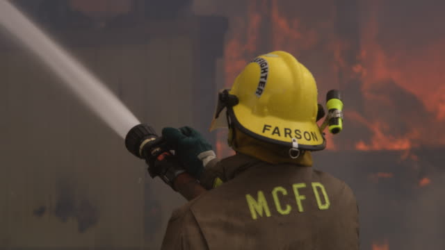 fireman adjusts the nozzle of a high pressure hose as he sprays a burning structure - myrtle creek stock videos and b-roll footage