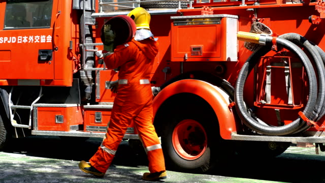 4k fireman carrying fire hose in front of fire engine - fire station stock videos & royalty-free footage