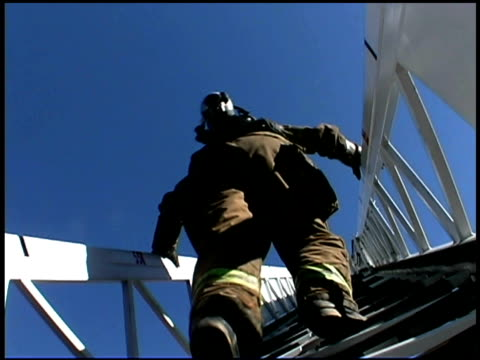 vidéos et rushes de fireman climbing ladder on blue sky - échelle