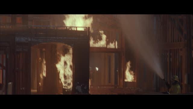 ms, pan fireman fighting fire at burning housing structure under construction at night - breitwandformat stock-videos und b-roll-filmmaterial
