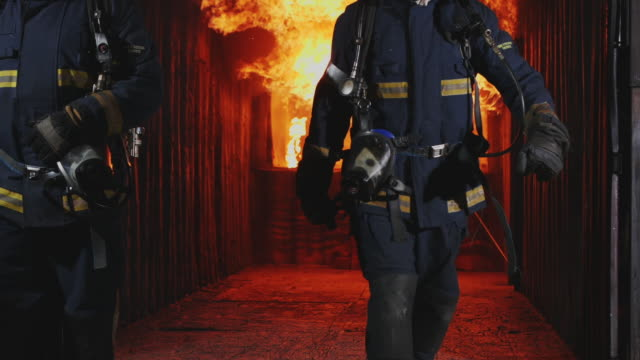 slo mo fireman, fire fighter walking towards the camera with fire is raging in the background. - fire station stock videos & royalty-free footage