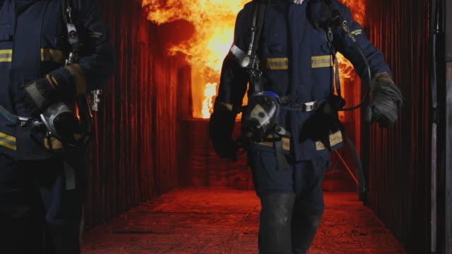 vídeos y material grabado en eventos de stock de slo mo fireman, bombero caminando hacia la cámara con fuego está furioso en el fondo. - parque de bomberos