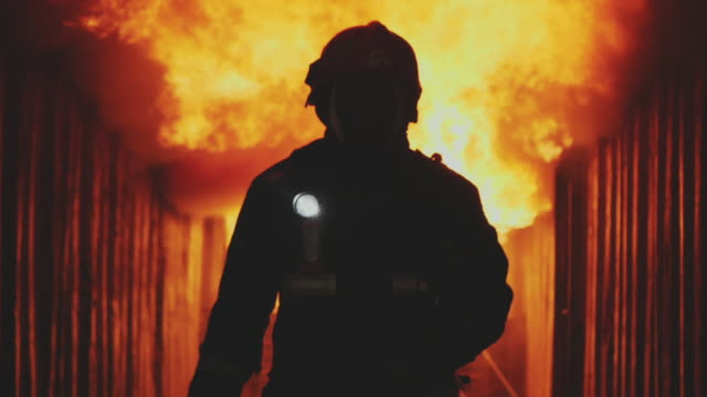 slo mo fireman, fire fighter walking towards the camera with fire is raging in the background. - helmet stock videos & royalty-free footage